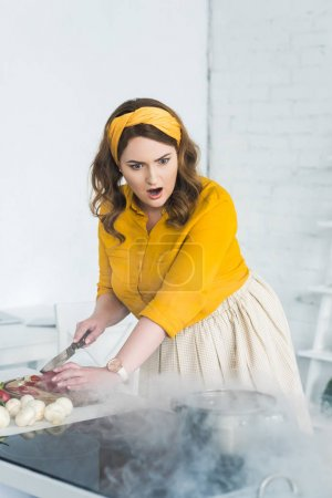 shocked beautiful woman looking at burning pan on electric stove at kitchen