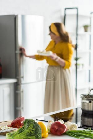 Photo for Woman taking plate from fridge with vegetables on foreground in kitchen - Royalty Free Image