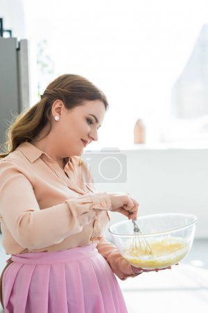 Photo for Side view of beautiful woman whisking dough in kitchen - Royalty Free Image