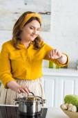 """Постер, картина, фотообои """"привлекательная женщина, проверка времени на наручные часы рядом с Пан на электрическая плита в кухне"""""""
