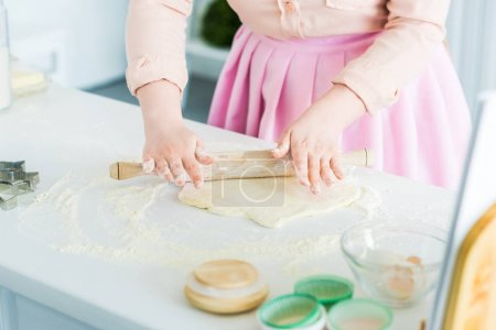 cropped image of woman rolling dough with rolling pin in kitchen