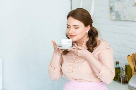 belle femme reniflant café les yeux fermés dans cuisine