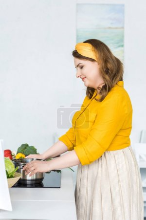 side view of beautiful woman cooking at electric stove in kitchen