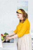"""Постер, картина, фотообои """"вид сбоку красивая женщина приготовления пищи на электрическая плита в кухне"""""""
