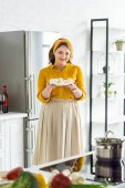 smiling beautiful woman holding plate with mushrooms at kitchen