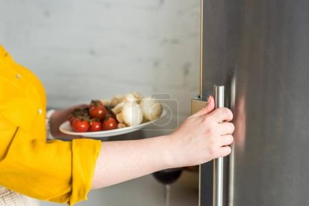 cropped image of woman opening fridge and holding plate with mushrooms and tomatoes in kitchen