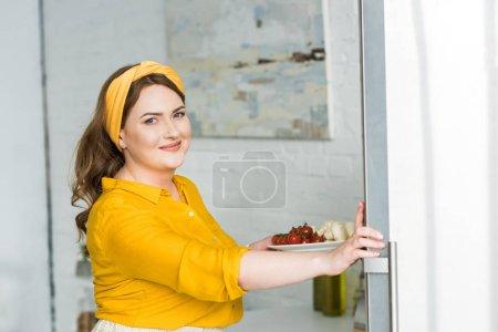 Photo pour Belle femme qui maintiennent la plaque avec des légumes à la cuisine - image libre de droit