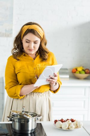 beautiful woman using tablet in kitchen