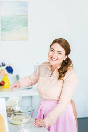smiling beautiful woman pouring milk into bowl with flour at kitchen