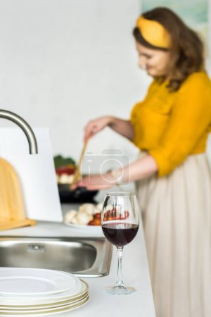 beautiful woman cooking vegetables with glass of wine on foreground in kitchen