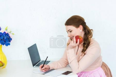 beautiful woman writing something to notebook and holding apple at kitchen