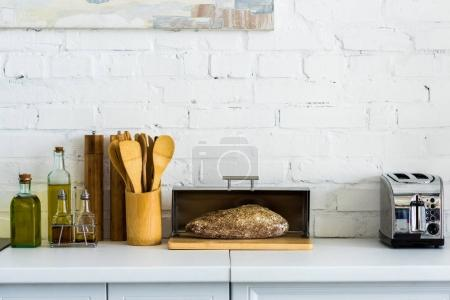 bread in breadbasket and toaster on kitchen counter