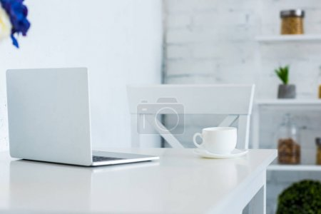 laptop and cup of coffee on white table kitchen