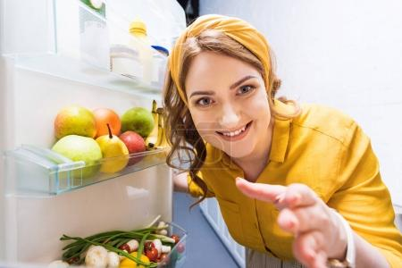 Photo for Beautiful smiling woman reaching hand in fridge at kitchen - Royalty Free Image