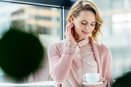 portrait of smiling thoughtful woman with cup of coffee