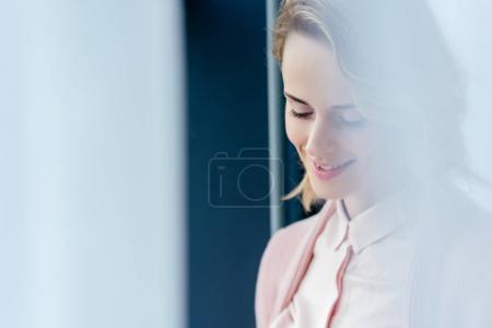Photo for Portrait of beautiful smiling woman in pink blouse and jacket looking away - Royalty Free Image