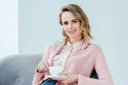 portrait of smiling woman in pink blouse with aromatic cup of coffee in hands