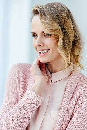 portrait of beautiful smiling woman in pink blouse and jacket looking away
