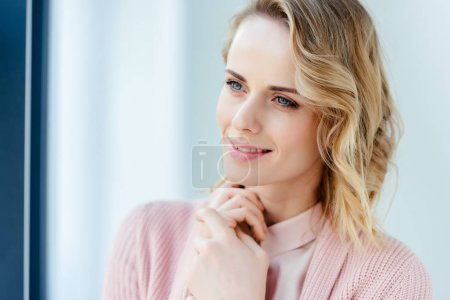 portrait of beautiful pensive woman in pink blouse and jacket looking away