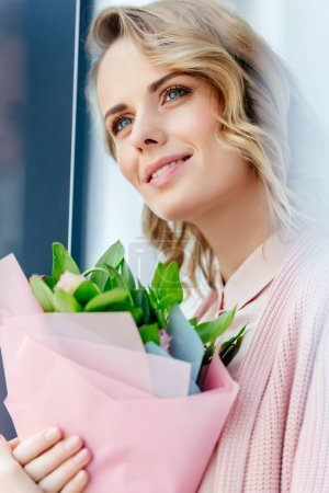 portrait of beautiful woman with bouquet of flowers looking away