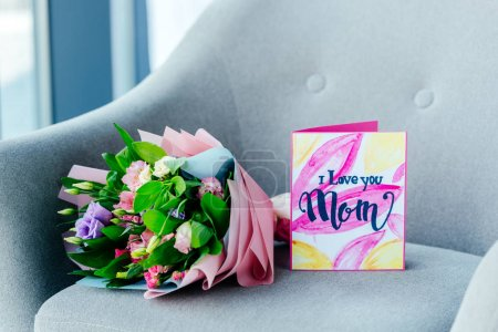close up view of wrapped bouquet of flowers and i love you mom greeting postcard on armchair, mothers day concept