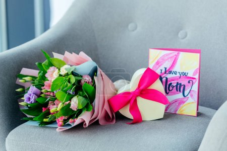 close up view of wrapped bouquet of flowers, heart shaped gift and i love you mom postcard on armchair, mothers day concept