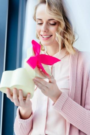 Photo for Happy woman opening heart shaped gift box in hands, mothers day holiday concept - Royalty Free Image