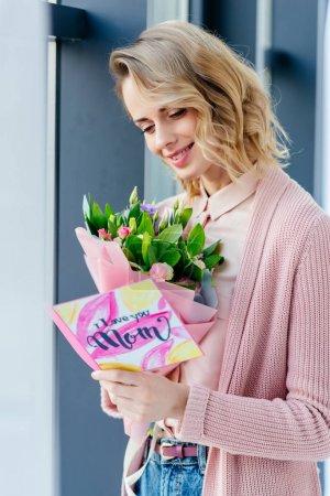 Photo pour Femme souriante avec bouquet de fleurs lecture je t'aime maman carte postale, concept de fête des mères - image libre de droit