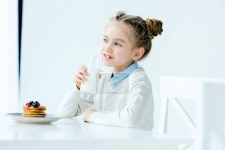Portrait d'enfant mignon avec le verre de lait à la main et crêpes maison avec du miel et des baies sur table