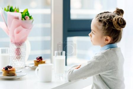side view of child sitting at table with bouquet of flowers, glass of milk and homemade pancakes
