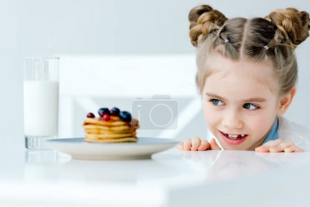 Photo for Selective focus of little kid looking at homemade pancakes with berries and honey on table - Royalty Free Image
