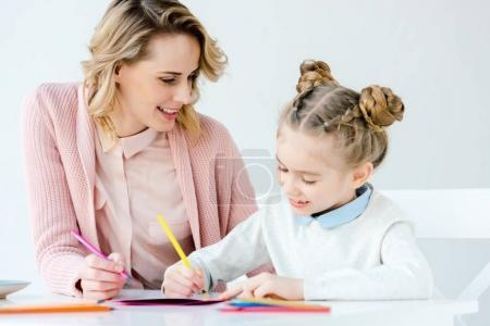 smiling mother and daughter making greeting postcard together at table