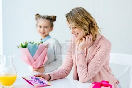 selective focus of happy mother looking at greeting postcard and daughter with bouquet of flowers standing near by, mothers day concept