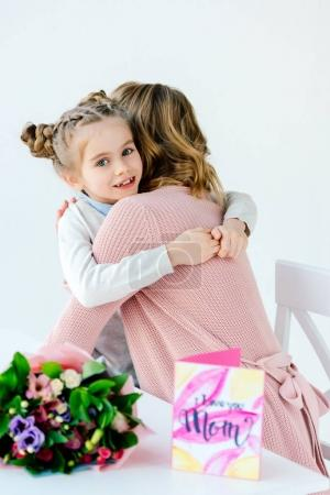 kid and mother hugging each other with gifts on table, mothers day holiday concept