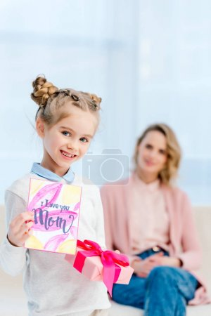 adorable daughter showing postcard on happy mothers day