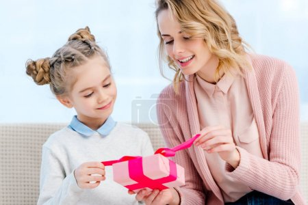 mother and daughter opening gift box on happy mothers day