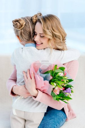 happy mother hugging daughter and holding bouquet on happy mothers day
