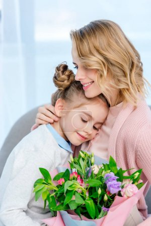 mother hugging daughter and holding bouquet on happy mothers day