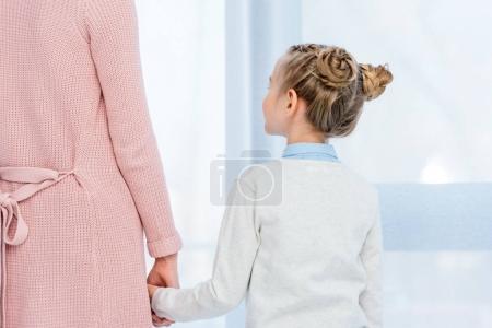 Foto de Imagen recortada de madre e hija en casa cogidos de la mano - Imagen libre de derechos