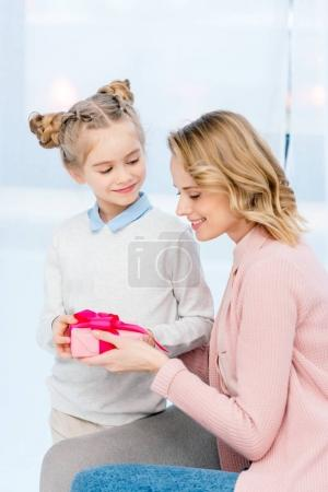 daughter presenting mother gift box on happy mothers day