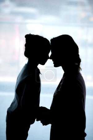 silhouettes of mother and daughter touching with foreheads at home