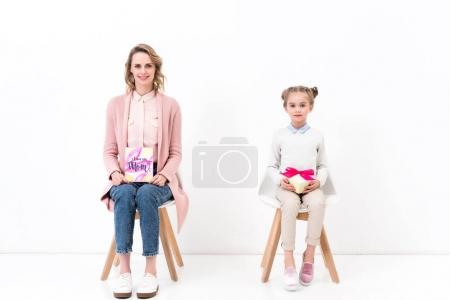 mother and daughter sitting on chairs with postcard and bouquet, happy mothers day concept
