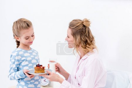 daughter giving mother pancakes on happy mothers day