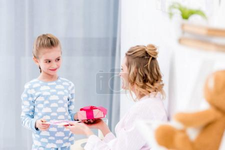 happy daughter greeting mother on happy mothers day at home