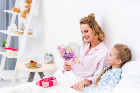 happy mother reading daughters postcard on happy mothers day