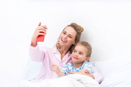 smiling mother and daughter taking selfie with smartphone on bed at home