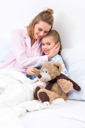 mother hugging daughter with teddy bear on bed at home