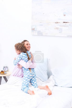happy mother and daughter hugging in bedroom