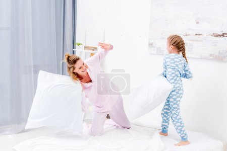 happy mother and daughter having fun and fighting with pillows at home