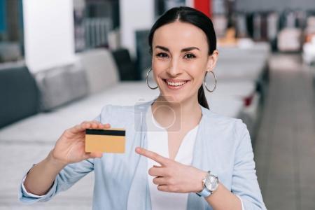 Photo pour Femme souriante pointant la carte de crédit en main dans le magasin de meubles avec matelas disposés - image libre de droit